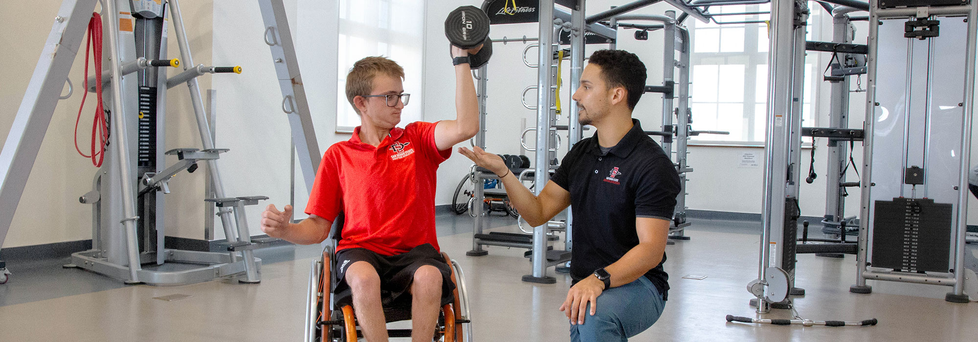 Adaptive Athletics - Young man in weelchair instructed technique on working out with a dumbell
