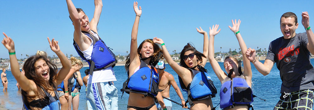 Watersports students jumping in joy