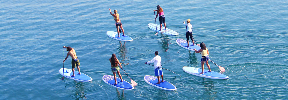 Group of students paddleboarding on the ocean at MBAC