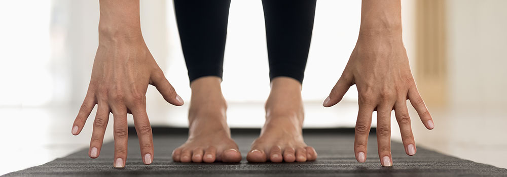 Woman stretching - hands touching the mat