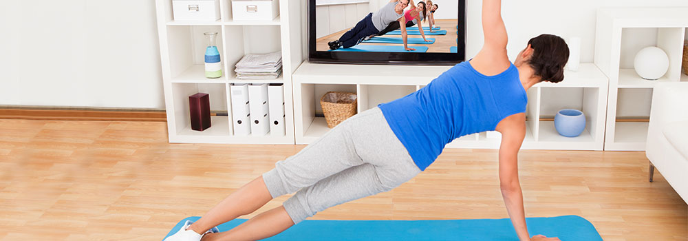Woman following fitness instructions on a TV