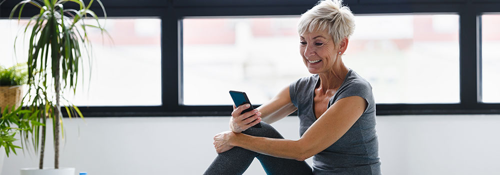 Older woman in fitness gear looking on her phone
