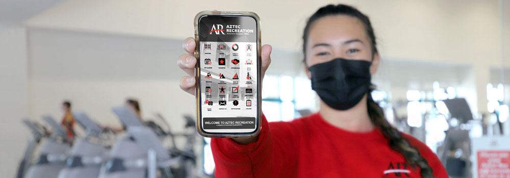 Aztec Recreation employee holding smartphone with AR App open