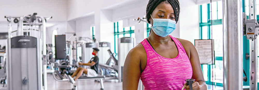 Female working out at ARC Express with face mask on