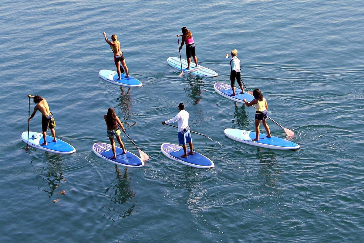 Men running towards the ocean with surfboards